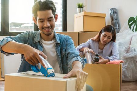 Pareja joven asiática empacando una caja de cartón grande para mudarse a una nueva casa, concepto de mudanza y búsqueda de casa Foto de archivo