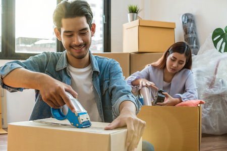 Asian young couple packing big cardboard box for moving in new house, Moving and House Hunting concept Foto de archivo