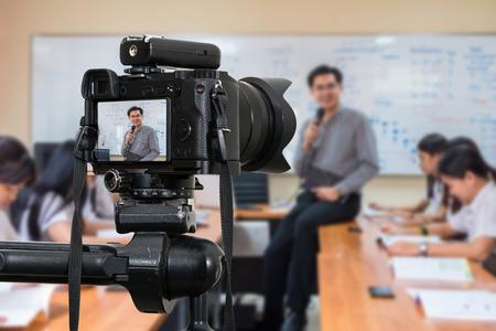 Profesjonalny aparat cyfrowy bezlusterkowy na statywie, nagrywający blog wideo azjatyckiego nauczyciela w klasie