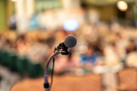 Mikrofon über dem abstrakten unscharfen Foto des Konferenzsaals oder des Seminarraums mit dem Hintergrund des Publikums, des Bildungs- und Lernkonzepts Standard-Bild