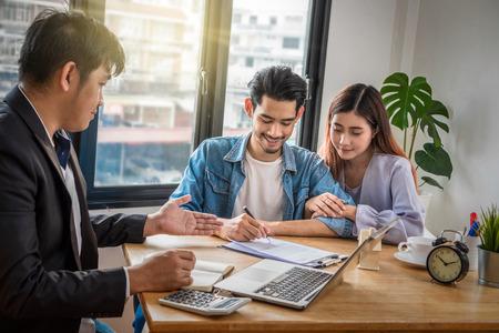 Asiatisches junges Paar unterschreiben Kontakt des Hauskaufs oder der Hausvermietung, die Verkaufsvertreter die Bedingung im Dokument auf dem Arbeitsraumtisch im neuen Haus, Umzugs- und Hausjagdkonzept anbieten lassen,