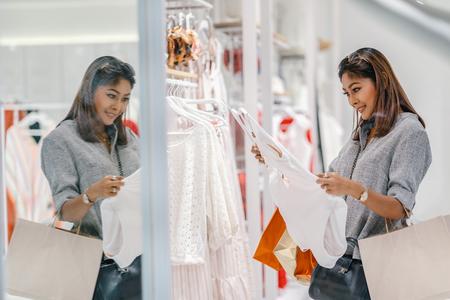 Asiatische Frau, die die Unterwäsche im Ladengeschäft mit glücklicher Aktion im Kaufhaus sucht und auswählt
