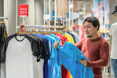Smart asian man with beard choosing clothes in clothing store at shopping center, looking t-shirts sale 20% off, Fashion and Consumerism Concept. Stock Photo