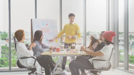 Gerente joven asiático que presenta las ideas creativas frente al grupo de empresarios asiáticos y multiétnicos con traje casual en acción feliz en el lugar de trabajo moderno Foto de archivo