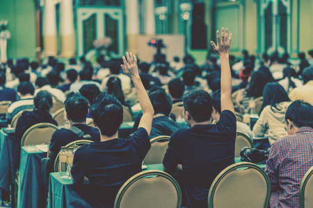 Rear view of Audience showing hand to answer the question from Speaker on the stage in the conference hall or seminar meeting, business and education concept