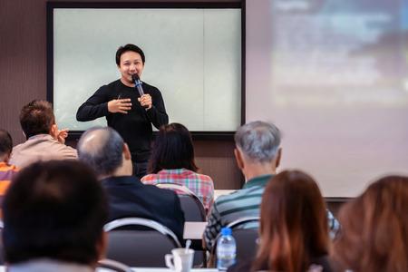 Altoparlante asiatico o conferenza con abito casual sul palco di fronte alla stanza che presenta con lo schermo nella sala conferenze o nella sala riunioni del seminario, concetto di business e istruzione