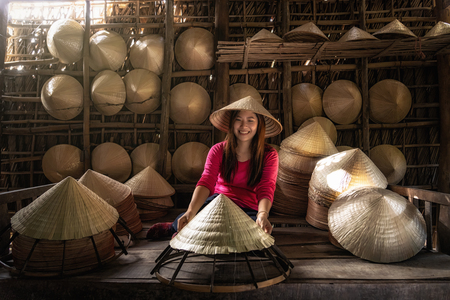 Asian traveler female craftsman making the traditional vietnam hat in the old traditional house in Ap Thoi Phuoc village, Hochiminh city, Vietnam, traditional artist concept Banco de Imagens