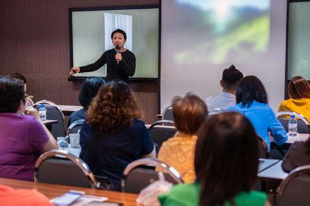 Asiatischer Sprecher oder Vortrag mit Freizeitanzug auf der Bühne vor dem Raum, der mit dem Bildschirm im Konferenzsaal oder Seminarraum präsentiert, Geschäfts- und Bildungskonzept