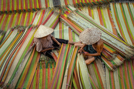 Top view of old Vietnamese lover craftsman making the traditional vietnam mats in the old traditional village at dinh yen, dong thap, vietnam, tradition artist concept