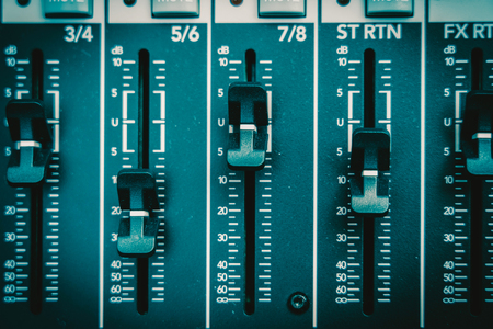Close up of an audio mixer, vintage film style, music equipment concept Фото со стока