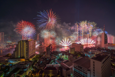 Fantastic Multicolor Firework exploding over the Bangkok Cityscape river side for Celebration, Business architecture and celebration and happy new year and merry christmas concept