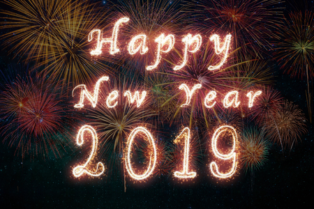 Happy new year 2019 written with Sparkle firework on fireworks with dark background, celebration and greeting cards concept Banco de Imagens