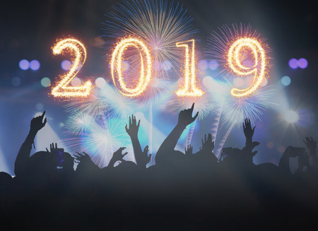2019 written with Sparkle firework on Concert crowd in silhouettes of Music fanclub with show hand action for celebrate with fireworks, Happy new year celebration concept