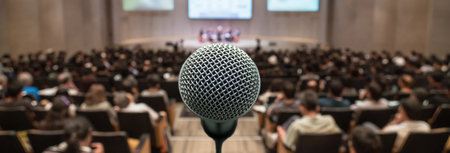 Banner and web page or cover template of Microphone over the Abstract blurred photo of conference hall or seminar room with attendee background, Business meeting concept Imagens