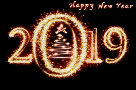 Happy new year 2019 and christmas tree written with Sparkle firework on dark background, celebration and greeting cards concept Banco de Imagens