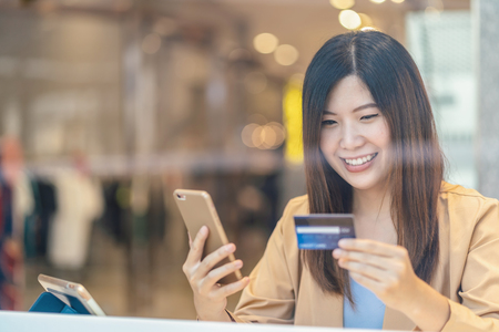 Asian woman using credit card with mobile phone for online shopping in department store over the clothes shop store background, technology money wallet and online payment concept, credit card mockup Banco de Imagens