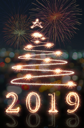 Happy new year 2019 and christmas tree written with Sparkle firework over the multicolors background, happy new year concept