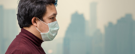 Banner of Asian man wearing the face mask against air pollution at the balcony of High Apartment which can see pollution and heavy fog over the bangkok cityscape background, healthcare concept