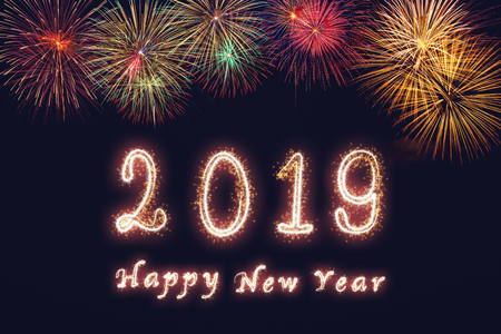 Happy new year 2019 written with Sparkle firework on fireworks with dark background, celebration and greeting cards concept Stock Photo