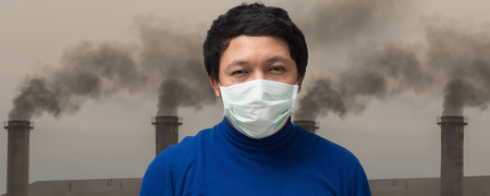 Banner of Asian man wearing the face mask against air pollution over the Smokestack Factory with black smoke on the sky with cloud, healthcare industry and pollution concept
