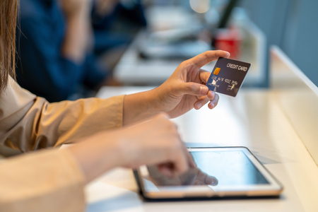 Closeup Asian woman using credit card with tablet for online shopping in department store over the clothes shop store background, technology money wallet and online payment concept, credit card mockup