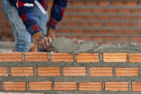Closeup hand professional construction worker laying bricks in new industrial site. construct industry and masonry concept
