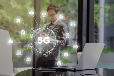 5G technology with various icon internet of thing over technology laptop and tablet with paper coffee cup on the working space in modern office with asian businessman standing and using mobile