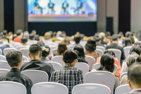 Rear view of Audience listening Speakers on the stage in the conference hall or seminar meeting, business and education about investment concept