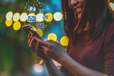 Closeup hand of Asian woman using smartphone and touching screen for social netwrok media with number of Like, Love, comment, people and fovorite icon at outdoor park, Business and Lifestyle concept Banco de Imagens