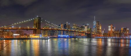Panorama scene of New york Cityscape with Brooklyn Bridge over the east river at the twilight time, USA downtown skyline, Architecture and building with tourist concept