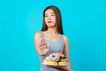 Attractive Asian young woman doing no action with donuts on isolated blue color background, weight loss and avoid junk food for dieting and Healthy concept, copy space and studio