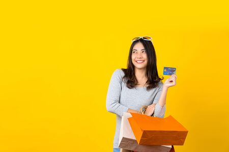 Happy Asian smiling woman using credit card and Carrying a shopping coloful bag for presenting online shopping on isolated yellow color background, copy space and studio, black friday season sale
