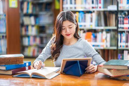 Estudiante joven asiático en traje casual haciendo la tarea y usando teblet de tecnología en la biblioteca de la universidad o colega con varios libros y papelería sobre el fondo del estante de libros, regreso a la escuela