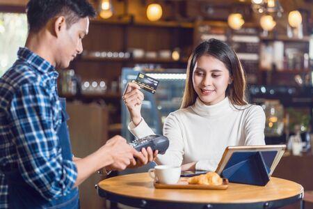 Cliente asiático mujer pagando con tarjeta de crédito a través de tecnología sin contacto al propietario de una pequeña cafetería asiática en la mesa femenina en el café, propietario de una pequeña empresa y puesta en marcha en el concepto de cafetería