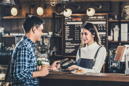 Asian customer man paying via contactless channel by mobile banking application to Asian Small business owner at the table in coffee shop, Small business owner and startup in coffee shop concept Banque d'images