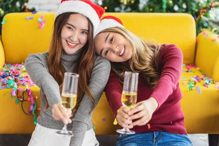 LGBTQ couple asian happiness women wearing colorful red sweaters holding and cheering in christmas party with xmas trees, asian