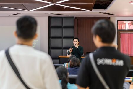 Asian Speaker or lecture with casual suit on the stage presenting via projector screen in the conference hall or seminar meeting room to Audience, business education and Seminar concept