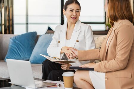 Two asian businesswomen happiness Reach an agreement by shaking hand together after successful deal the business contract in modern office or coworking space, success partnership concept