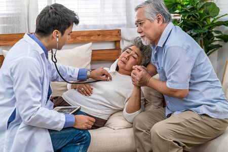 Closeup Doctor hand using stethoscope for auscultate Asian grandparent patient in house, service Life insurance at home, healthcare with Long live, Prevent epidemic and Covid19 Disease concept