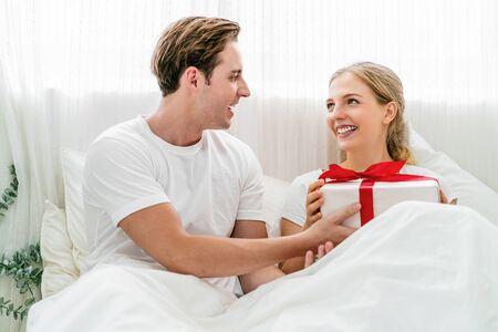 Caucasien Un couple heureux d'amoureux célèbre ensemble dans la chambre à coucher à la maison, une jeune femme reçoit son petit ami un coffret cadeau pour une surprise, une surprise pour la Saint-Valentin, un anniversaire ou Noël.