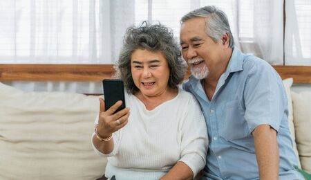 Asian couple Grandparent taking Video call to grandchild or taling selfie with happy feeling by mobile phone in house, Long live and Elderly society,Warm family and happiness,social distancing concept 写真素材