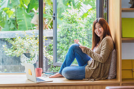 Asian business woman using technology laptop and working from home with say hello or bye, freelance and entrepreneur, creative design and blogger, social distance and self responsibility concept