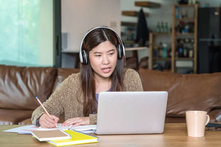 Asian business woman using technology laptop and headphone for working from home in indoor house by video conference call, startups and business owner, social distance and self responsibility
