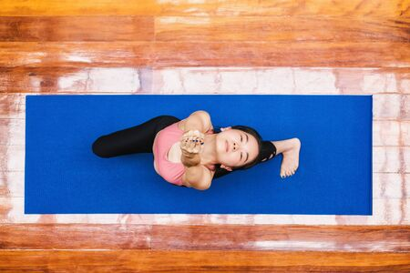 Top view Asian woman practicing yoga from home when Covid19 outbreak, healthy or Meditation Exercise, workout at home, coronavirus pandemic and quarantine, sports and healthcare in concept