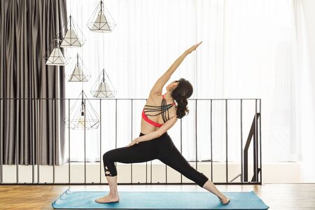 Asian woman practicing yoga from home when Covid19 outbreak and lockdown, healthy or Meditation Exercise, yoga workout at home, coronavirus pandemic and quarantine, sports and healthcare concept
