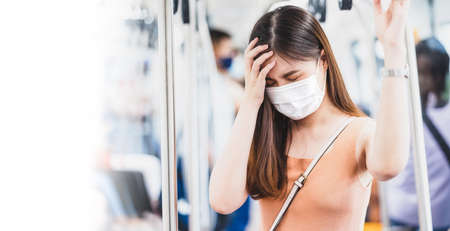 Young Asian woman passenger wearing surgical mask and Having a headache in subway train when traveling in big city at Covid19 outbreak, Infection and Pandemic,new normal and illness prevention concept 免版税图像