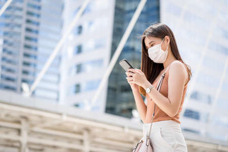 Young Asian woman using smart mobile phone in outside big city at Covid19 outbreak, Infection and Pandemic, commuter and transportation, social distancing and new normal concept 免版税图像