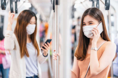 Young Asian woman passenger wearing surgical mask and talking together via smart mobile phone in subway train when traveling in big city at Covid19 outbreak, social distancing and new normal concept