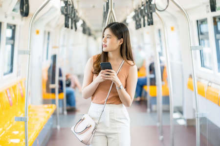Young Asian woman passenger using smart mobile phone and looking to outside of subway train when traveling in big city, commuter and transportation concept