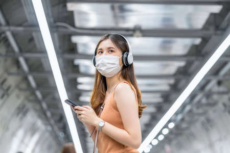 Young Asian woman passenger wearing surgical mask and listening music via smart mobile phone in subway train interchange when traveling in big city at Covid19 outbreak, Infection and Pandemic concept 免版税图像